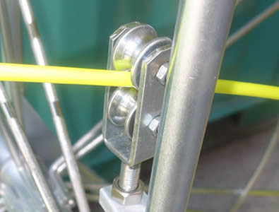 The rod guide of the duct rodder, with a yellow rod through it.